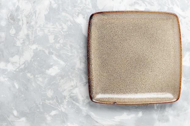Vue de dessus assiette carrée vide marron ed sur un bureau blanc