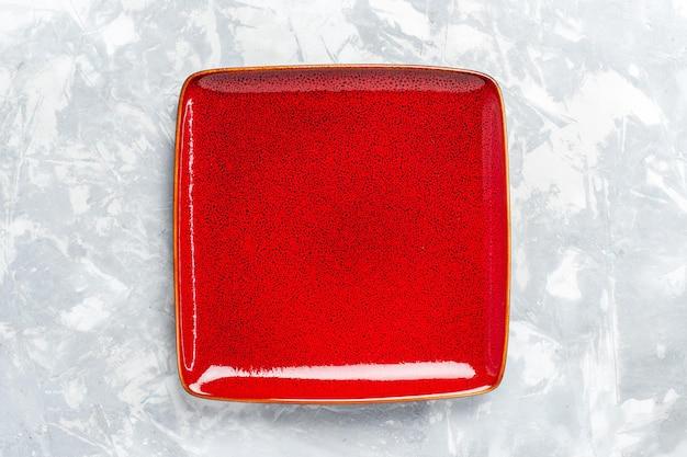 Vue de dessus assiette carrée vide rouge ed sur surface blanche