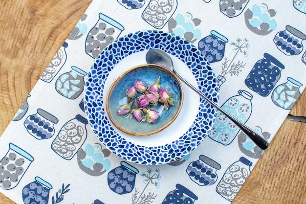 Vue de dessus assiette conçue avec de petites fleurs sur fond de bois cuisine design en verre photo couleur