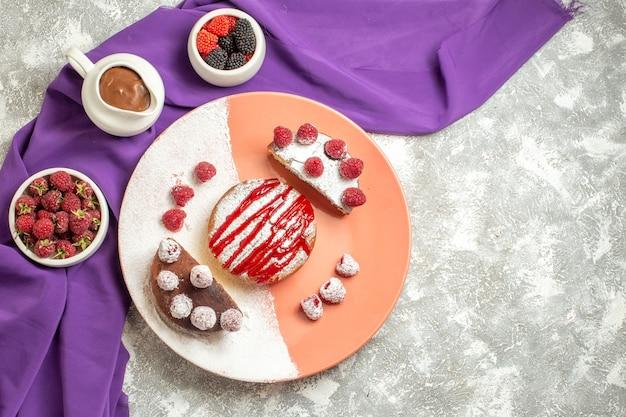 Vue de dessus de l'assiette de dessert sur une serviette violette avec des baies et du chocolat sur le côté sur fond de marbre