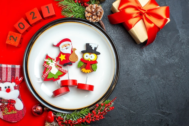 Vue de dessus de l'assiette à dîner accessoires de décoration branches de sapin et numéros chaussette de noël sur une serviette rouge à côté de cadeau sur une table noire