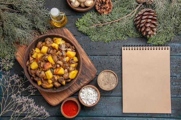 Vue de dessus de l'assiette du bol de nourriture de champignons et de pommes de terre sur la planche à découper à côté de différentes épices et d'un cahier sous une bouteille de bol d'huile de champignons blancs et de branches d'épinette avec des cônes