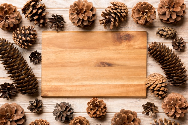Vue de dessus d'une assiette de fête avec des pommes de pin sur le concept de dîner en bois, nouvel an