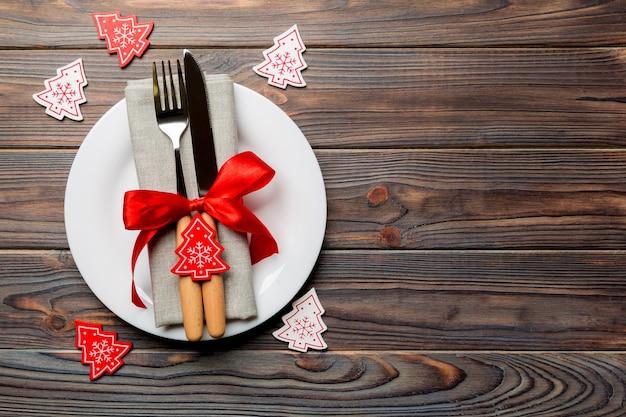 Vue de dessus de l'assiette, fourchette et couteau servi sur fond en bois décoré de noël