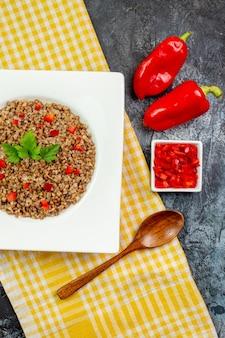 Vue de dessus d'une assiette intérieure de sarrasin cuit savoureux avec des poivrons sur une table gris clair