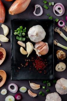 Vue de dessus de l'assiette de légumes comme l'oignon vert coupé à l'ail avec des épices d'œuf d'oignon sur fond marron