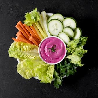 Vue de dessus de l'assiette avec légumes et sauce rose