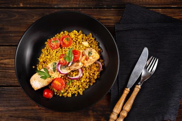 Vue de dessus d'une assiette noire avec sarrasin vert au curry, tomates cerises et filet de saumon préparé.