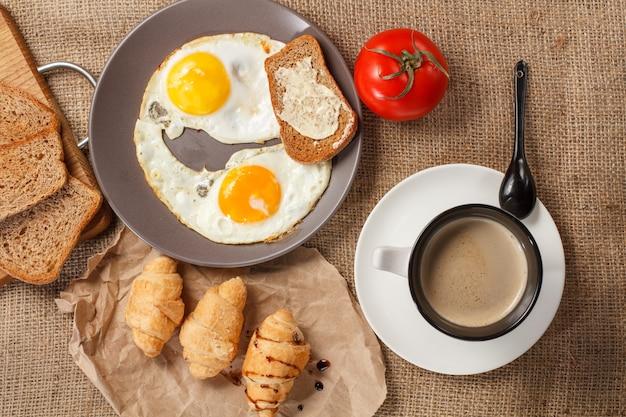 Vue de dessus de l'assiette avec œufs au plat, pain grillé, tomate fraîche, tasse de café noir, croissants, pain sur planche à découper en bois, tomate fraîche