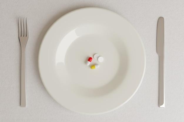Vue de dessus d'une assiette avec des pilules à côté d'un couteau et d'une fourchette sur blanc