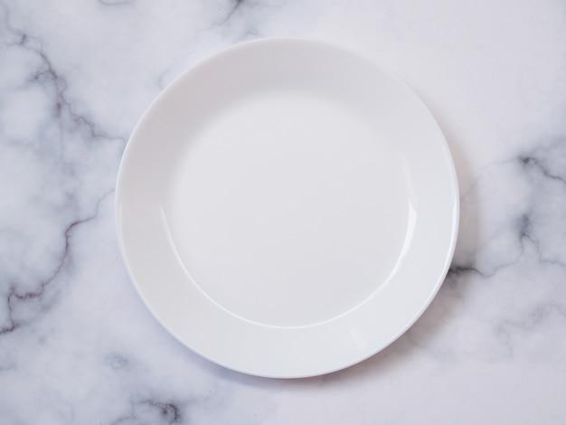Vue de dessus d'une assiette ou d'un plat blanc rond isolé sur une table en marbre.