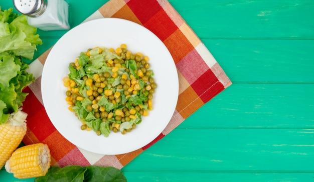 Vue de dessus de l'assiette de pois jaunes et de la laitue en tranches avec du sel de laitue aux épinards de maïs sur tissu et vert avec copie espace