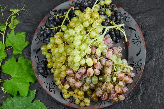 Vue de dessus d'une assiette de raisins mélangés autour des feuilles de vigne sur fond sombre. photo de haute qualité