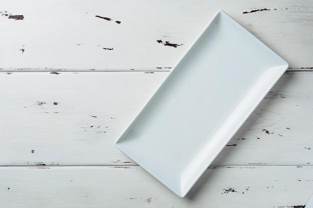 Vue de dessus d'une assiette rectangulaire blanche sur un fond en bois blanc.