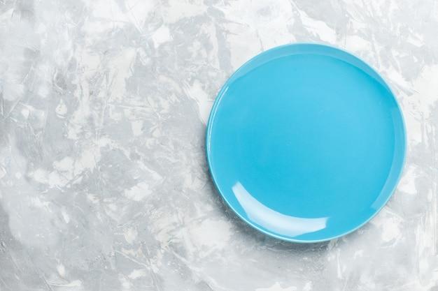 Vue de dessus assiette ronde vide bleu ed sur surface blanche