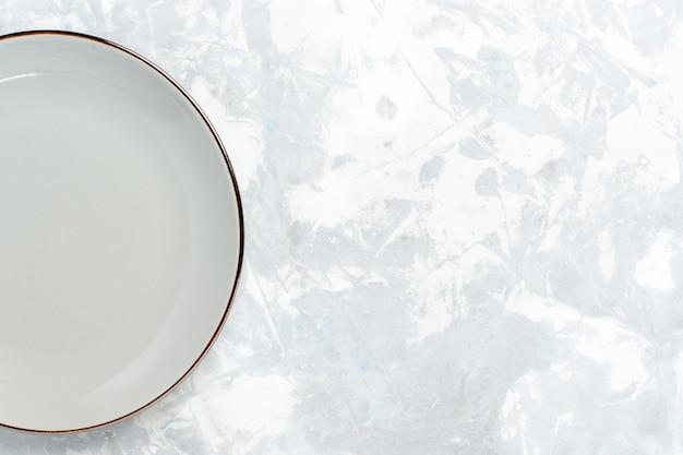 Vue de dessus assiette ronde vide sur un bureau blanc clair