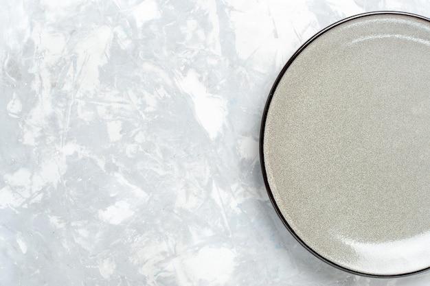 Vue de dessus assiette ronde vide gris ed sur surface blanche