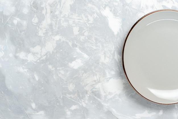Vue de dessus assiette ronde vide sur une surface blanche