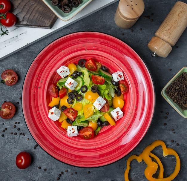 Vue de dessus assiette rouge de salade de légumes.