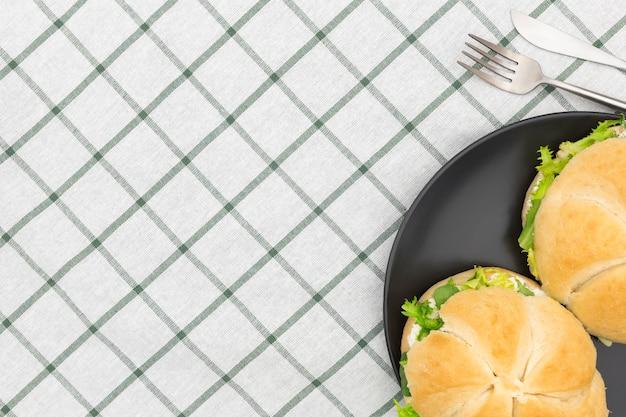 Vue de dessus de l'assiette avec des sandwichs et des couverts