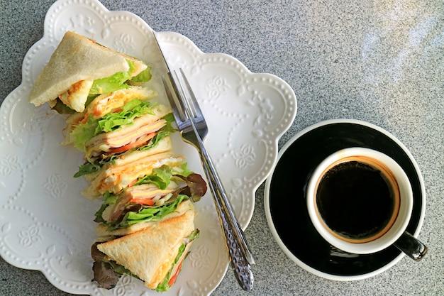Vue de dessus d'une assiette de sandwichs mixtes servis avec une tasse de café chaud aromatique