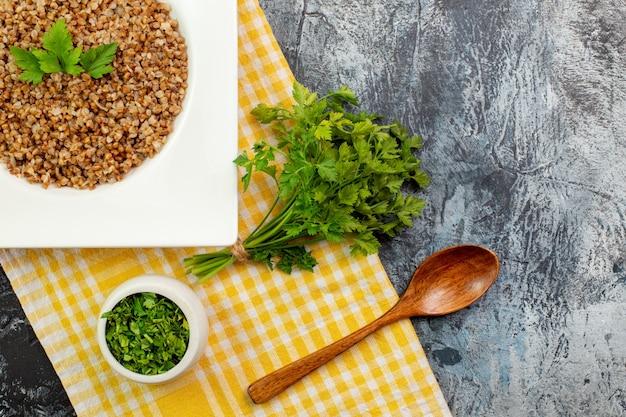 Vue de dessus d'une assiette de sarrasin cuit savoureux avec des verts sur une table gris clair