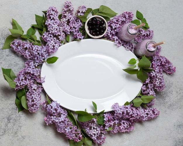 Vue de dessus assiette vide sur les fleurs de jacinthe avec smoothie