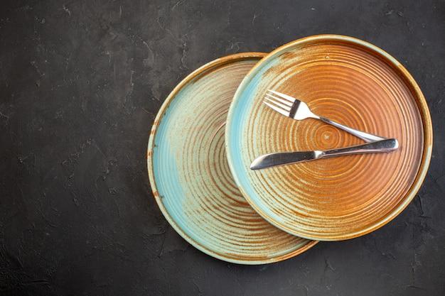 Vue de dessus des assiettes brunes avec un couteau et une fourchette sur une surface sombre