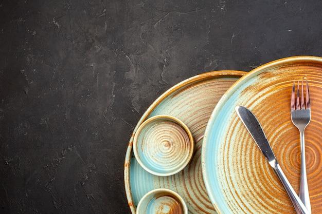 Vue de dessus des assiettes brunes avec de petites assiettes sur une surface sombre