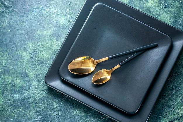 Vue de dessus assiettes carrées sombres avec des cuillères dorées sur des couverts de surface sombre