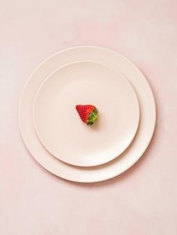 Vue de dessus des assiettes en céramique avec une fraise sur fond pastel rose