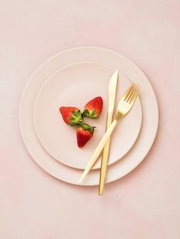 Vue de dessus des assiettes en céramique avec des fraises et des couverts dorés sur fond pastel rose