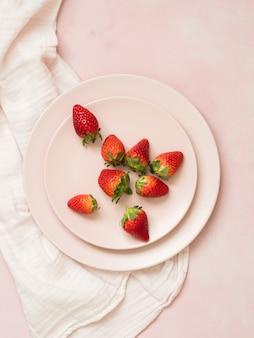 Vue de dessus des assiettes en céramique avec des fraises sur fond pastel rose