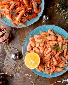 Vue de dessus des assiettes de crevettes servies avec des citrons