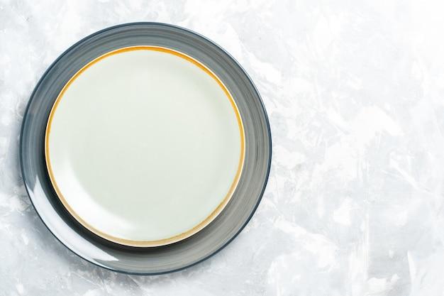Vue de dessus des assiettes rondes vides sur une surface blanche