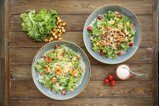 Vue de dessus des assiettes à salade césar avec crevettes et tranches de poulet