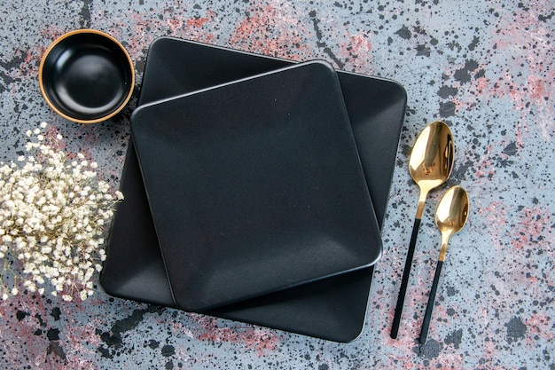 Vue de dessus assiettes sombres avec cuillères dorées sur fond clair couverts table alimentaire nuances de couleur dîner service restaurant