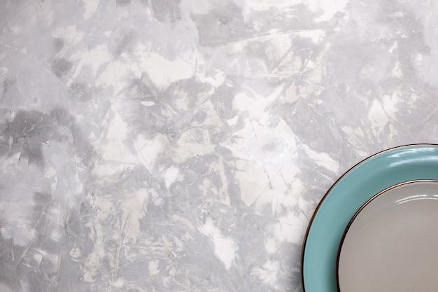 Vue de dessus des assiettes vides en verre sur une surface blanche