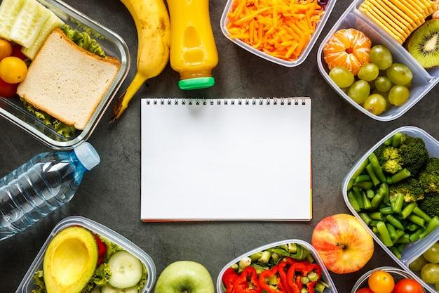 Vue de dessus assortiment d'aliments en lots cuits avec un cahier vide