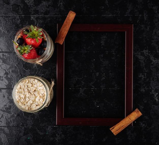 Vue de dessus de l'assortiment d'avoine de nuit avec des baies et des flocons d'avoine dans des bocaux en verre et cadre photo vide en bois sur fond noir