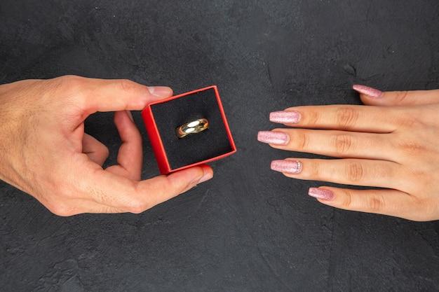 Vue de dessus atteignant les mains main masculine tenant l'anneau dans la boîte main féminine sur fond sombre