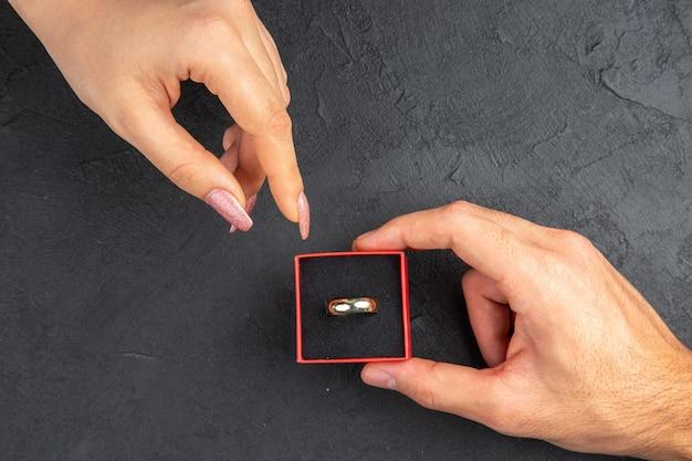 Vue de dessus atteignant les mains main masculine tenant l'anneau dans la boîte main féminine