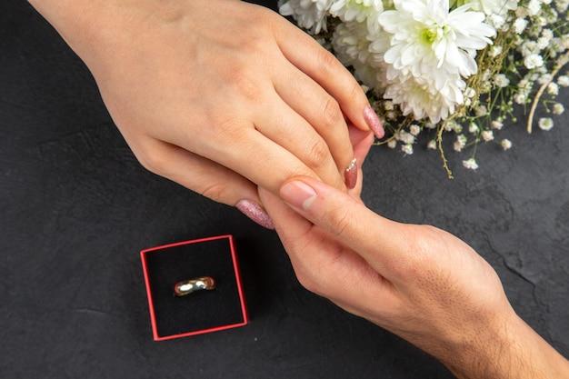 Vue de dessus atteignant les mains mâle main tenant femelle main bague de fiançailles bouquet de fleurs