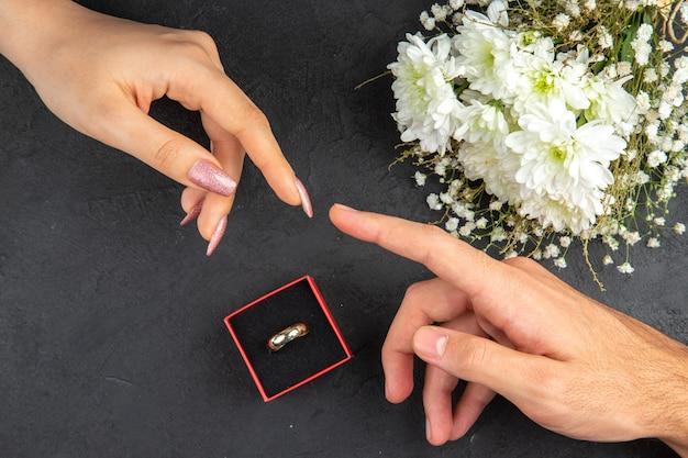 Vue de dessus atteignant les mains mâles et femelles mains bague de fiançailles bouquet de fleurs sur fond sombre