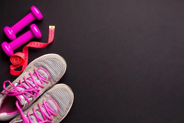 Vue de dessus des attributs de sport rose sur fond sombre