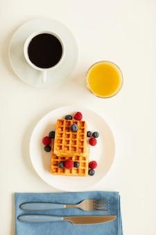 Vue de dessus au délicieux petit-déjeuner gastronomique avec des gaufres sucrées et du jus d'orange à côté d'une tasse de café noir sur table blanche
