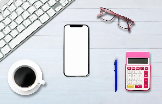 Vue de dessus au-dessus de l'ordinateur portable de téléphone sur le plancher de bois blanc de style bureau.
