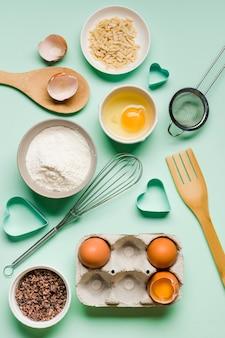 Vue de dessus au fouet avec des œufs et de la farine sur la table