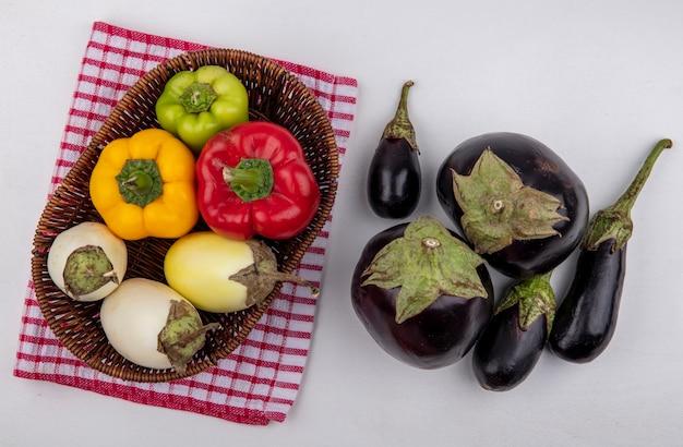 Vue de dessus aubergine blanche avec poivrons colorés dans un panier sur une serviette à carreaux rouge avec des aubergines noires sur fond blanc