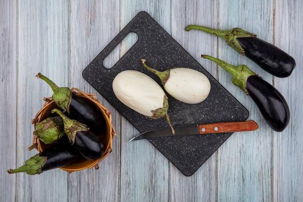 Vue de dessus d'aubergines blanches et couteau sur une planche à découper avec des nadia noirs dans le panier et sur fond de bois